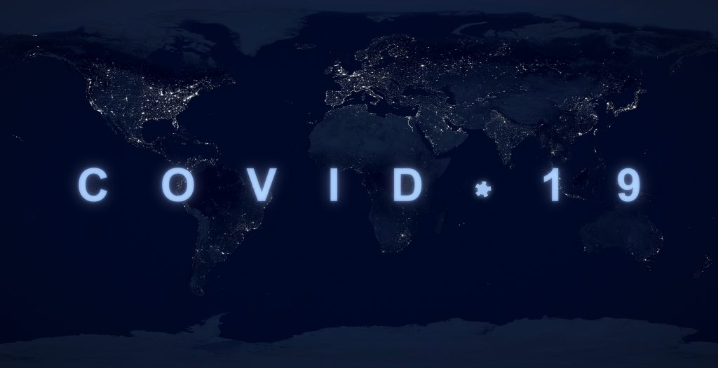 COVID-19 pandemic concept, name COVID on dark night planet map. World economy hit by coronavirus outbreak.